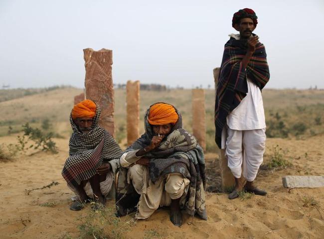Camel traders smoke near their camels early morning at the Pushkar Fair in Rajasthan