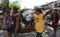 Residents cover their noses as they walk past debris with stench of corpses along a road in Tacloban city, devastated by Typhoon Haiyan in central Philippines