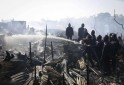Fire fighters try to extinguish a fire in a slum area in Mumbai