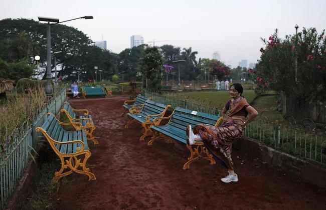 A woman wearing saree exercises in a park in Mumbai