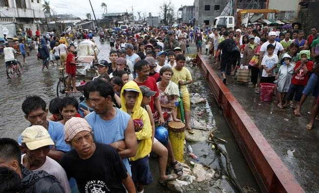 Typhoon victims queue for free rice at a businessman
