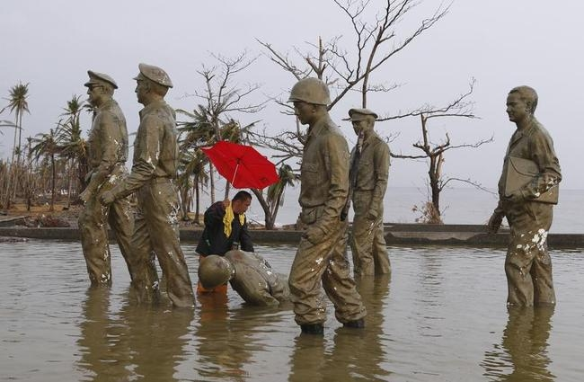 A resident inspects one of the statues at the U.S. General Douglas MacArthur shrine that fell at the height of super typhoon Haiyan last Friday in Palo, Leyte province