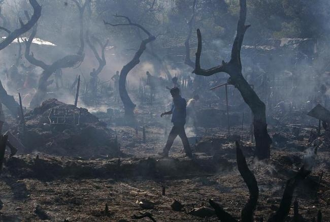 A resident walks through gutted huts after a fire in a slum area in Mumbai