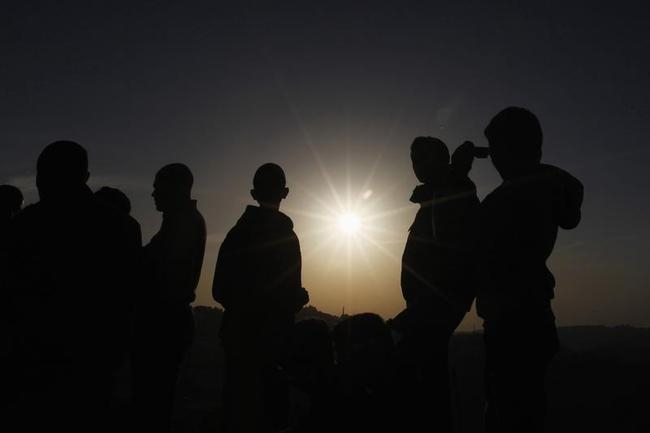 People observe a solar eclipse in Amman