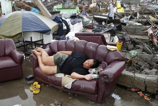A typhoon victim rests on a sofa at the ruins of her family