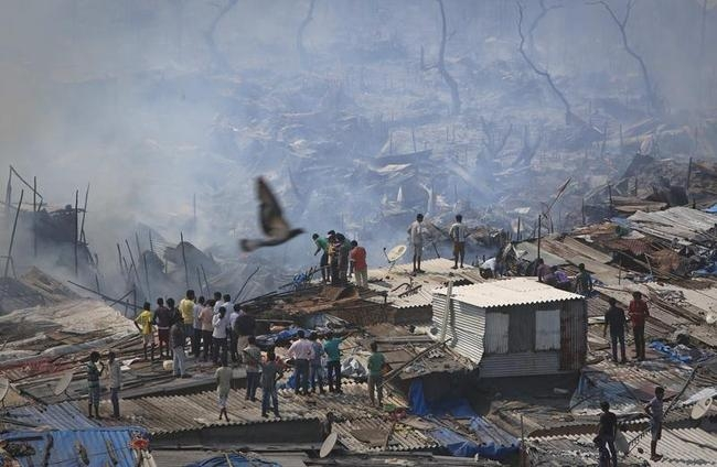 Residents watch as firefighters try to extinguish a fire in a slum area in Mumbai
