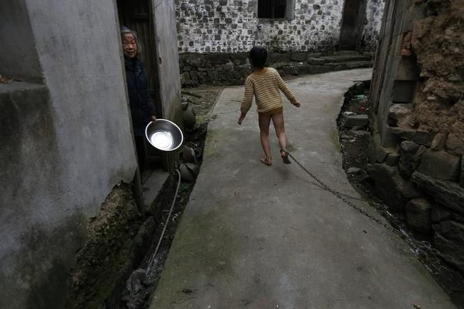 A boy runs past a neighbour along an alley outside his home as his father pulls on the chain locked around his ankle, in Zhejiang province