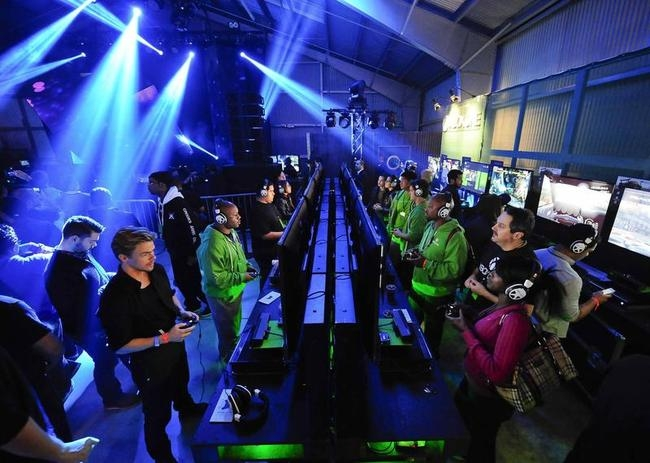 """Xbox fans play the latest games as DJ Joel Thomas Zimmerman """"Deadmau5"""" performs during the Xbox One fan celebration and launch party in Los Angeles, California"""