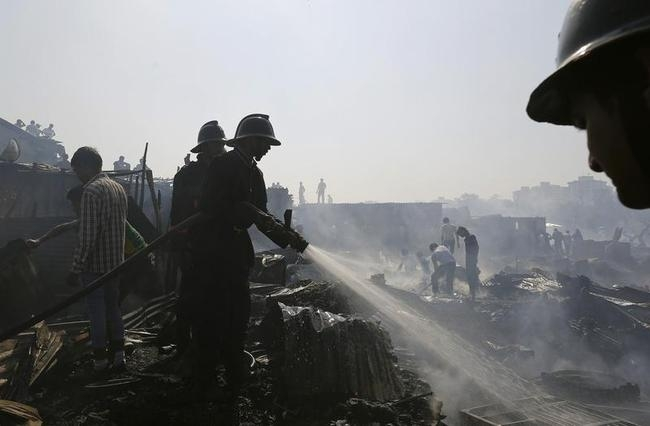 Firefighters try to extinguish a fire in a slum area in Mumbai