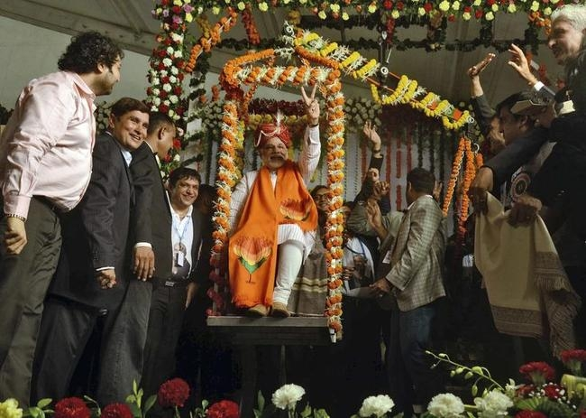 Hindu nationalist Narendra Modi sits on a weighing scale balanced with silver during the inauguration of the Mumbai Diamond Merchant Association