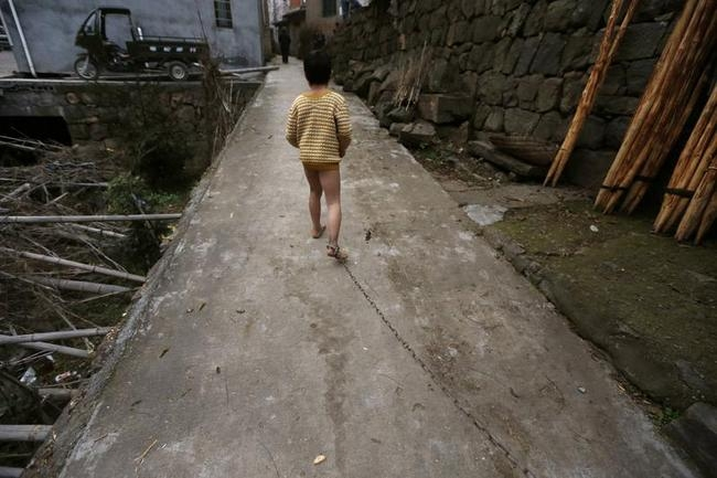 Eleven-year-old He Zili runs along an alley outside his home, as his father pulls on the chain locked around his ankle, in Zhejiang province