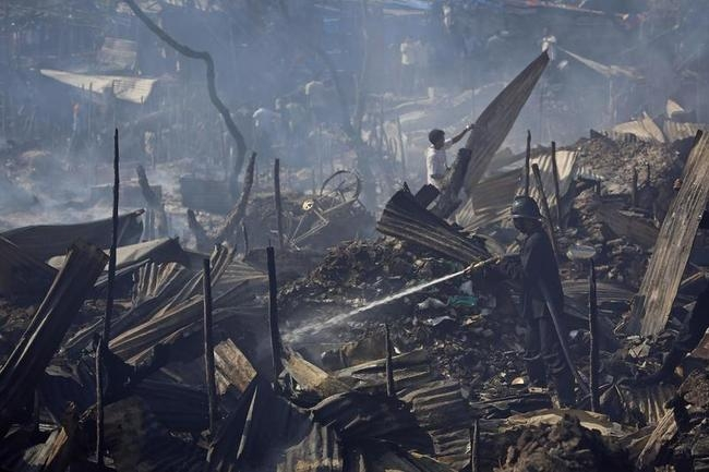 A firefighter tries to extinguish a fire in a slum area in Mumbai