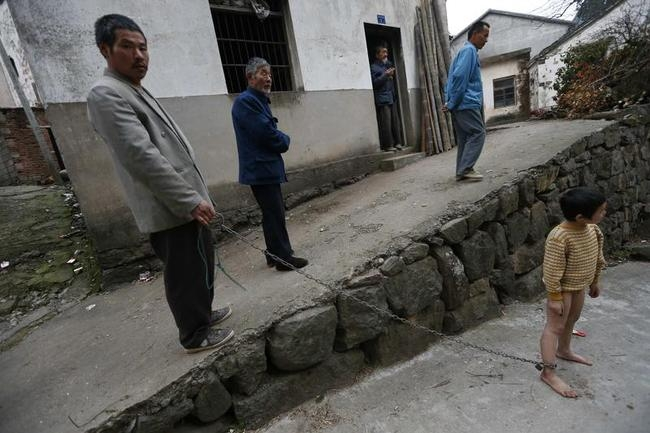 A boy stands outside his home as his father holds onto the chain locked around his ankle in Zhejiang province