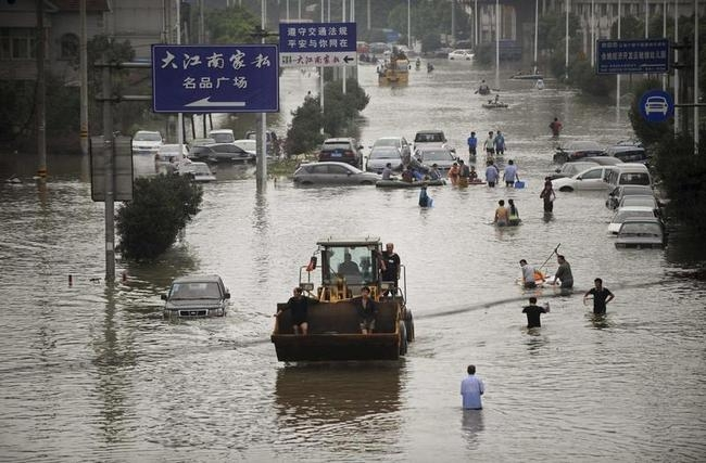 Residents travel on bulldozer as others walk amid a flooded street after Typhoon Fitow hit Yuyao