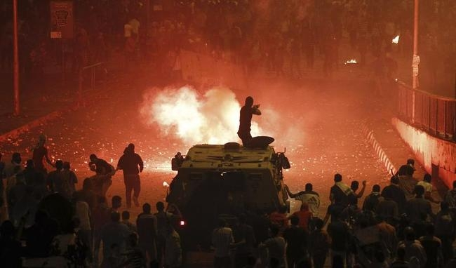 A riot police officer fires rubber bullets at members of the Muslim Brotherhood and supporters of ousted Egyptian President Mohamed Mursi in Cairo