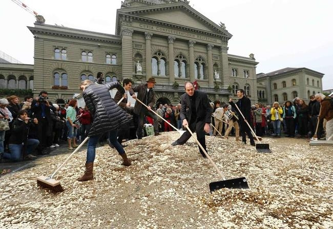 Committee members spread five cent coins over Federal Square during an event organised by the Committee for the initiative Grundeinkommen in Bern