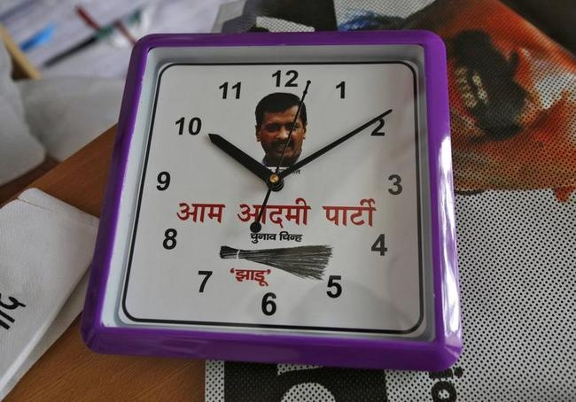 A wall clock carrying a portrait of Kejriwal, leader of the newly formed AAP, and the party symbol of a broom, lies on a table inside their party office in New Delhi