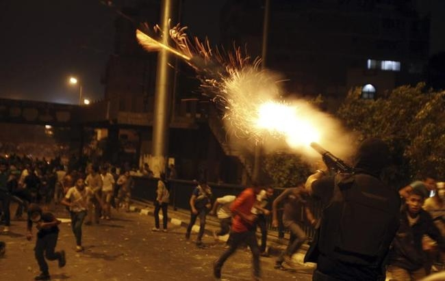 A riot police officer fires tear gas during clashes between anti-Mursi protesters, and members of the Muslim Brotherhood and ousted Egyptian President Mohamed Mursi supporters, in Cairo