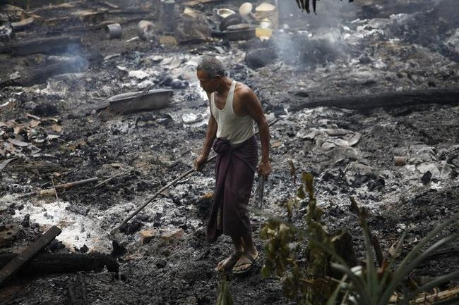A Muslim man searches for his belongings left behind of his burnt home at Thapyuchai village in Rakhine state