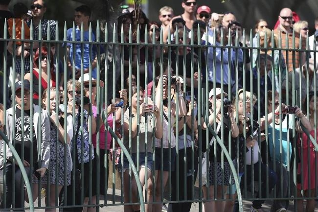 A crowd watches from behind a fence as Britain