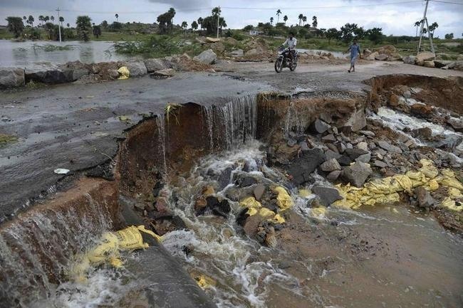 A man rides a motorcycle through a damaged flooded road after heavy rains on the outskirts of Hyderabad