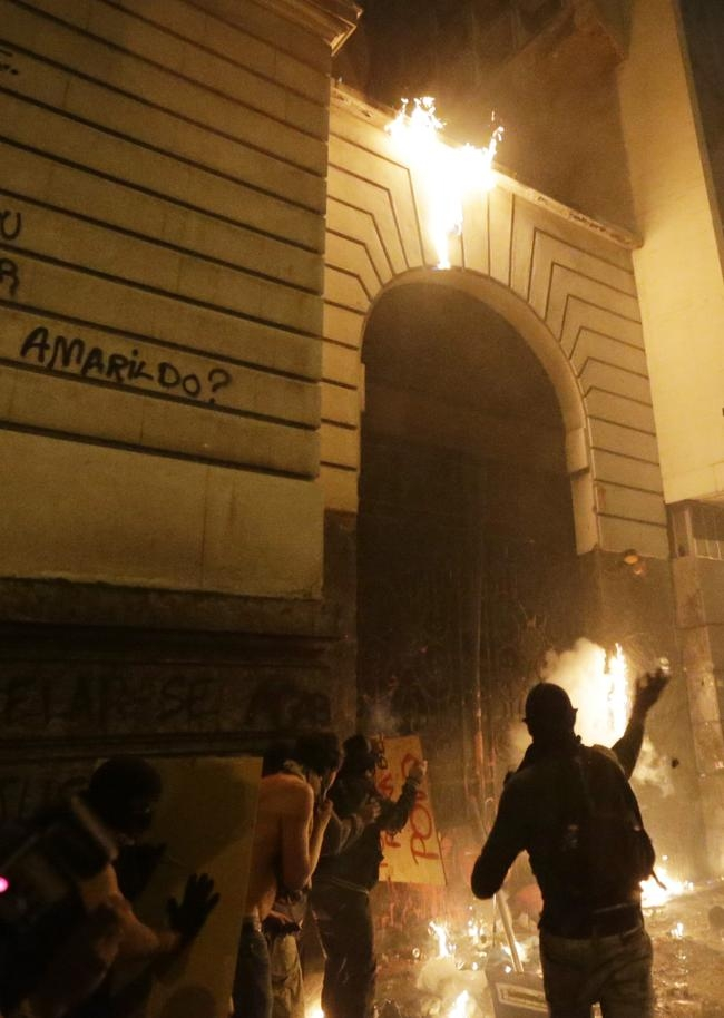 Demonstrators from the group called Black Bloc try to invade the Municipal Assembly during a protest supporting a teachers