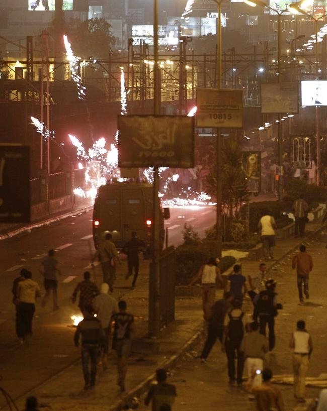 The Muslim Brotherhood and supporters of ousted Egyptian President Mohamed Mursi fire flares at anti-Mursi protesters and riot police during clashes along a road at The Ramsis square