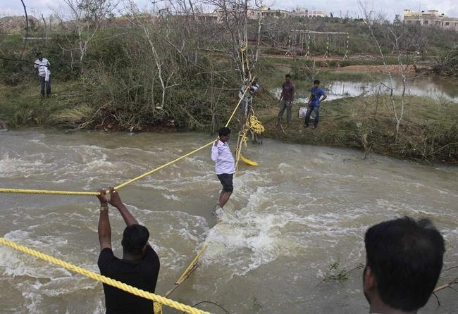People from a nearby village cross floodwaters using ropes connected to trees, at Ganjam district in Odisha