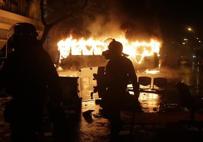 Riot policemen walk in front of a burning bus after demonstrators from the group called Black Bloc set fire to it during protest in Rio de Janeiro