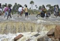 Villagers walk through a damaged flooded road after heavy rains on the outskirts of Hyderabad