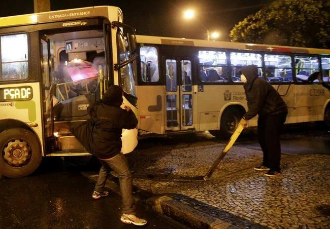 Black Bloc demonstrators attempt to set a bus on fire during a protest in Rio de Janeiro