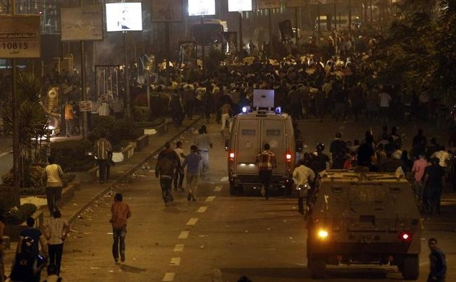 Riot police armoured personnel carriers fire rubber bullets and tear gas at members of the Muslim Brotherhood and supporters of ousted Egyptian President Mohamed Mursi during clashes in Cairo