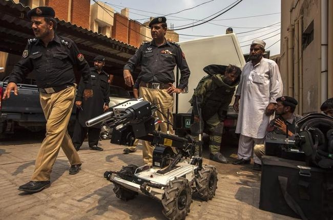 Malik, head of a police bomb disposal unit, watches his team display their equipment during a demonstration at the unit