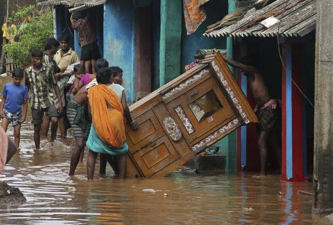 Villagers move their belongings to safer places in the flood-affected area of the Ganjam district in Odisha