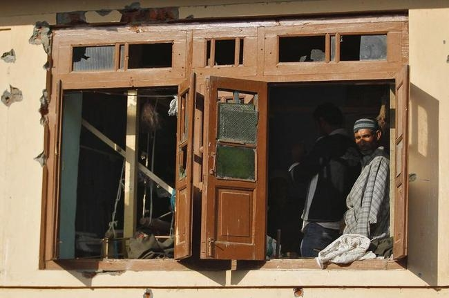 A Kashmiri man watches through a damaged window of a residential house after a gun battle on the outskirts of Srinagar