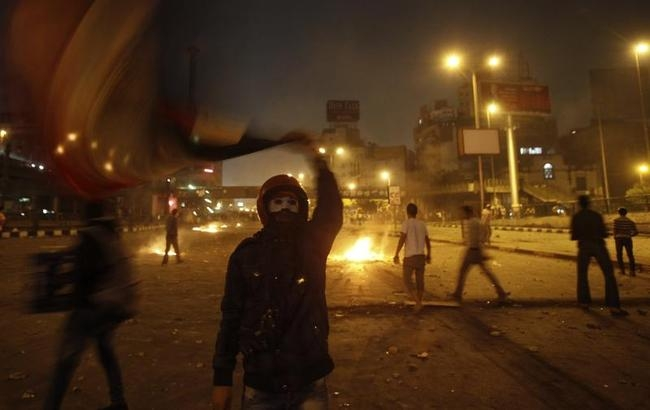 An anti-Mursi protester waves a national flag during clashes in Cairo
