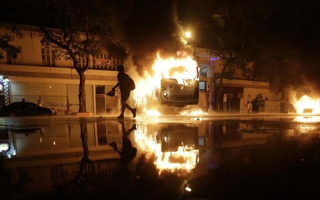A man walks past a burning bus after demonstrators from the group Black Bloc set fire to it during a protest in Rio de Janeiro