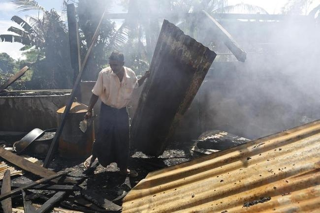 A man clears debris from the mosque that was burnt down in recent violence at Thapyuchai village