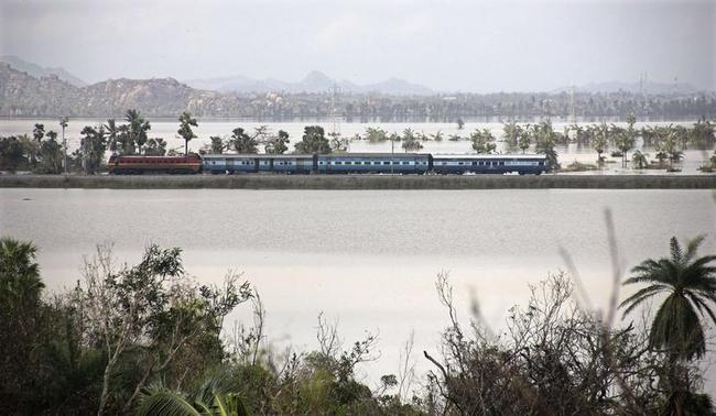 A train moves through a flood affected area of the Ganjam district in Odisha