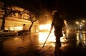 A riot policeman walks in front of a burning bus after demonstrators from the group Black Bloc set fire to it during protest in Rio de Janeiro