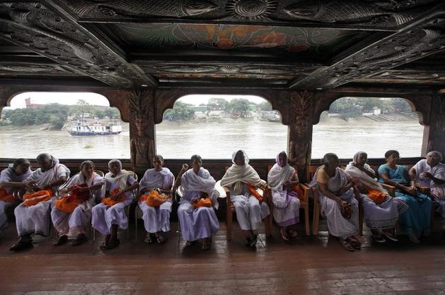 Widows sit with a member of a non-governmental organization as they travel on a boat on their way to visit the Belur temple on outskirts of Kolkata