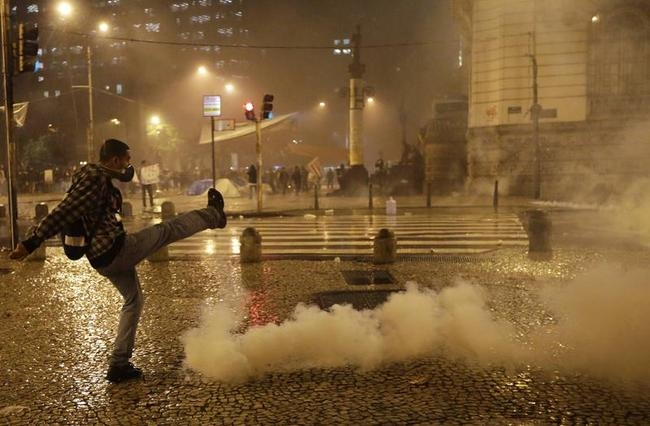 A demonstrator from the group called Black Bloc kicks a tear gas bomb as he clashes with riot police outside the Municipal Assembly during a protest supporting a teachers