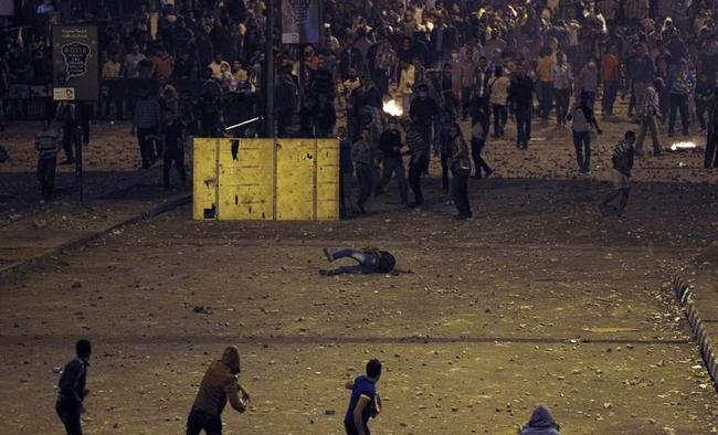 A man falls during clashes between anti-Mursi protesters, and members of the Muslim Brotherhood and ousted Egyptian President Mohamed Mursi supporters, in Cairo