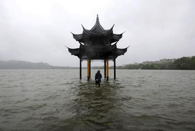 A man walks towards a flooded pavilion by the overflowing West Lake after Typhoon Fitow hit Hangzhou