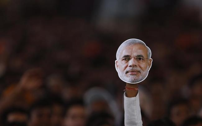 Supporter of BJP holds a mask of Hindu nationalist Modi during a rally being addressed by Modi in New Delhi