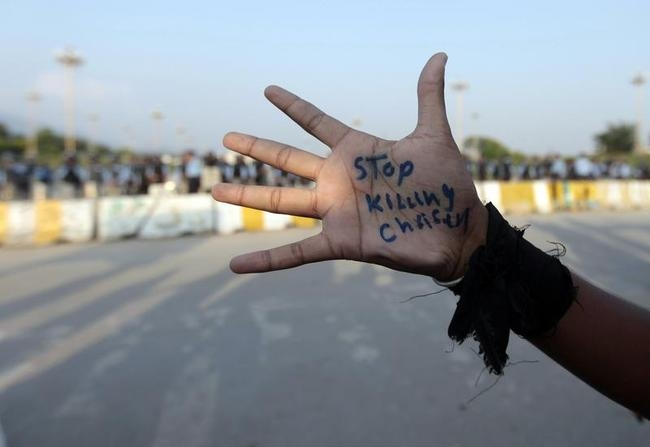 A member of the Pakistani Christian community attends a protest rally to condemn Sunday