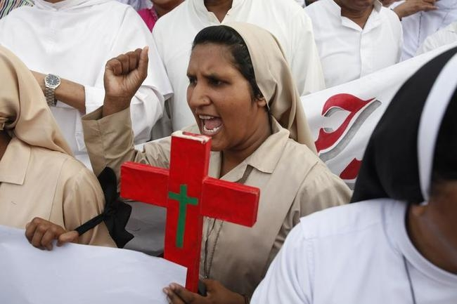 Member of Pakistani Christian community holds cross as she shouts slogan during protest rally to condemn Sunday