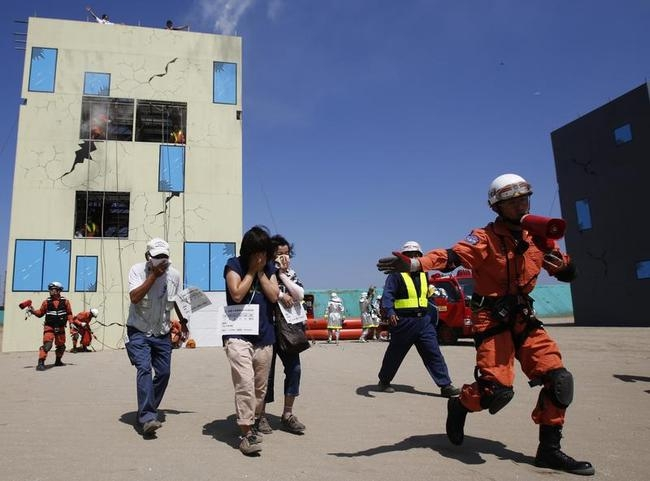 A rescue worker directs mock evacuees away from a building, which has smoke rising from it, during an annual anti-disaster drill based on scenarios of a major earthquake hitting Chiba