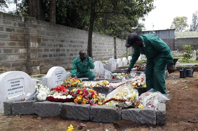 Cemetery workers arrange flowers on the grave of Kenyan journalist Ruhila Adatia Sood, who was killed in the Westgate shopping mall attack, during her funeral in Nairobi