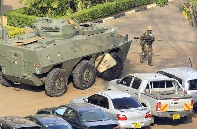 A Kenya Defence Forces soldier carrying a RPG walks past an armoured military vehicle in front of the Westgate shopping centre after an exchange of gunfire inside the mall in Nairobi